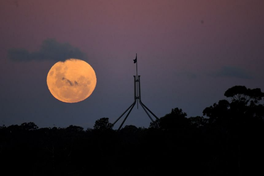 """The """"Super Blood Moon"""" rises over Parliament House in Canberra on May 26, 2021."""