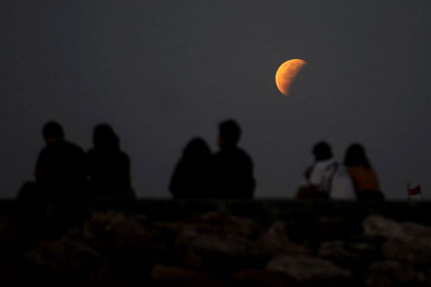 The moon is pictured from Sanur beach near Denpasar on the Indonesian resort island of Bali on May 26, 2021.