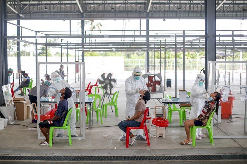 Thai health officials collecting samples during a coronavirus test drive at a Bangkok parking lot on Monday.