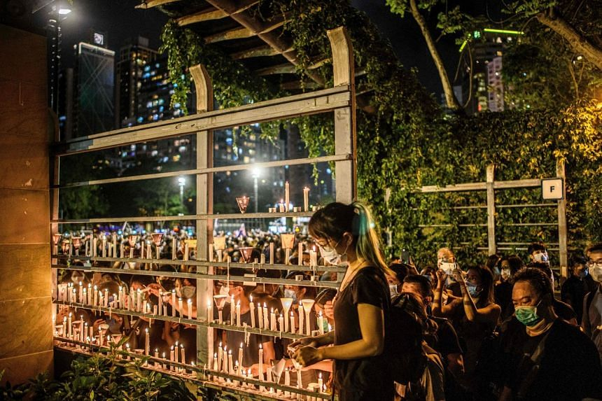 People light candles as they attend a vigil to mark the 1989 Tiananmen Square crackdown in Victoria Park, Hong Kong, on June 4, 2020.