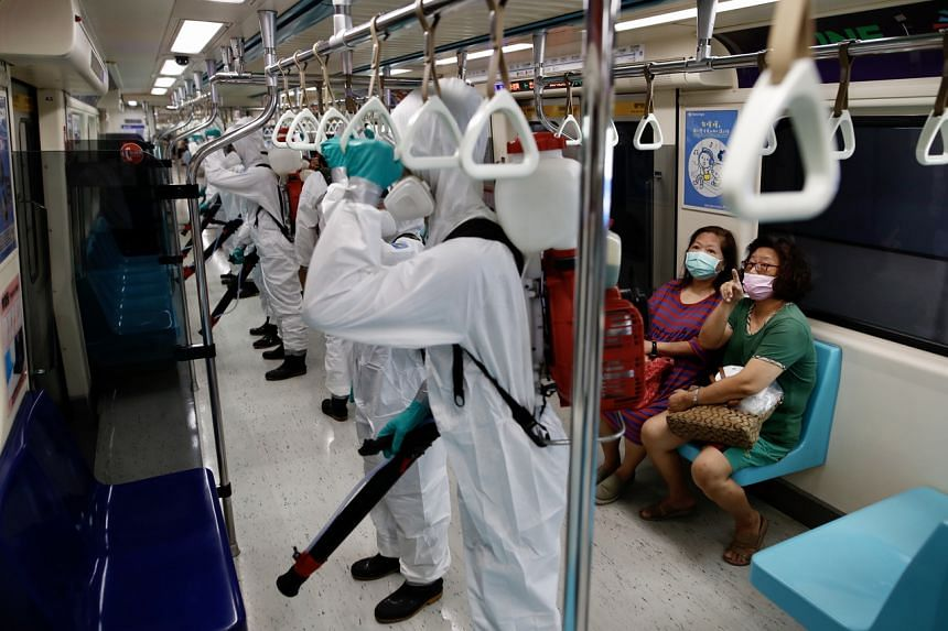 Members of Taiwan's military, tasked to spray disinfectant at train stations, on a train in Taipei on Tuesday.