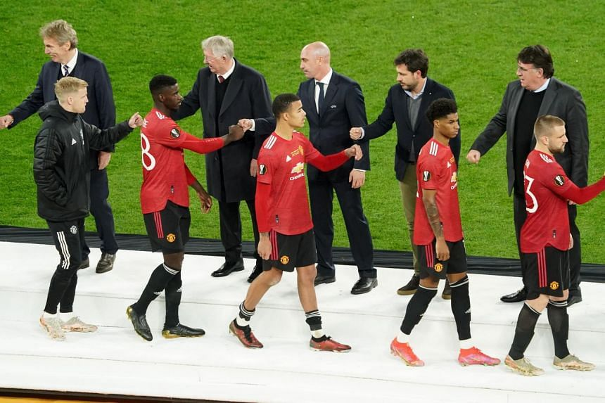 Manchester United's players look dejected as they wait to receive their runner up medals from UEFA president on May 26, 2021.