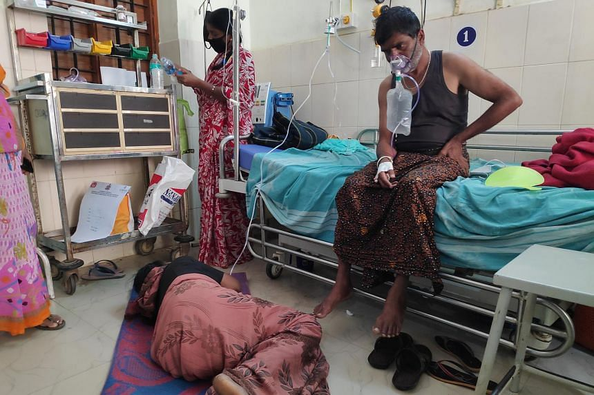 Mrs Laxmamma, a patient at the Chamarajanagar government district hospital, lying on the floor while sharing an oxygen outlet with another patient.