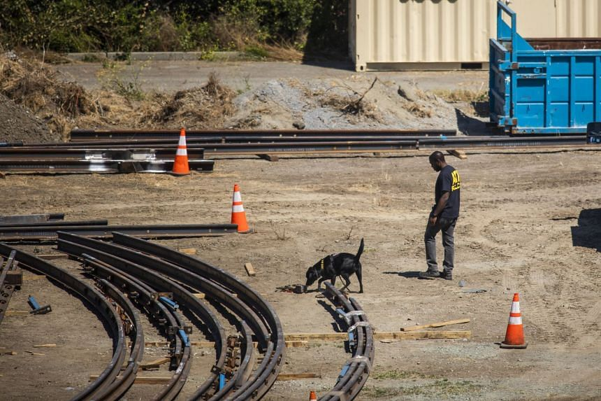 A law enforcement K-9 unit searches for evidence at the Valley Transportation Authority light-rail yard.