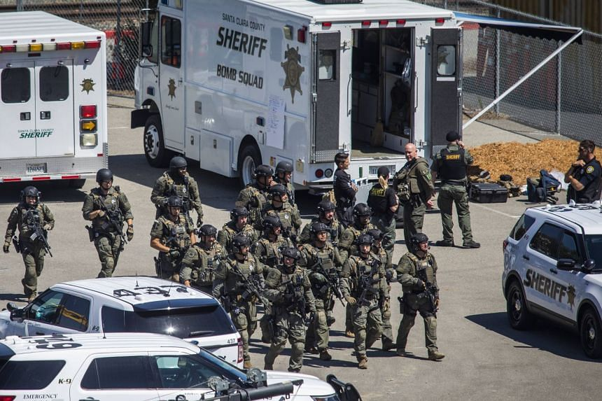 Tactical law enforcement officers move through the Valley Transportation Authority (VTA) light-rail yard.