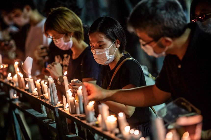 A file photo taken on June 4, 2020, shows people lighting candles during a remembrance to mark the Tiananmen Square crackdown, at Hong Kong's Victoria Park.