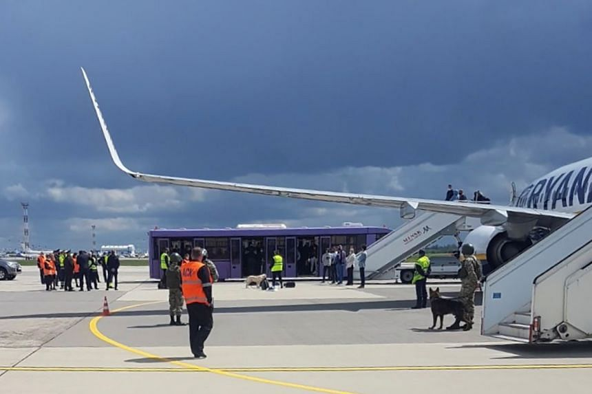 Airport personnel and security forces are seen on the tarmac in front of a Ryanair flight which was forced to land in Minsk, Belarus.