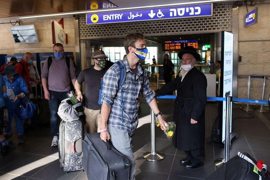 Tourists walk out of Israel's Ben Gurion International Airport as coronavirus restrictions ease, on May 27, 2021.