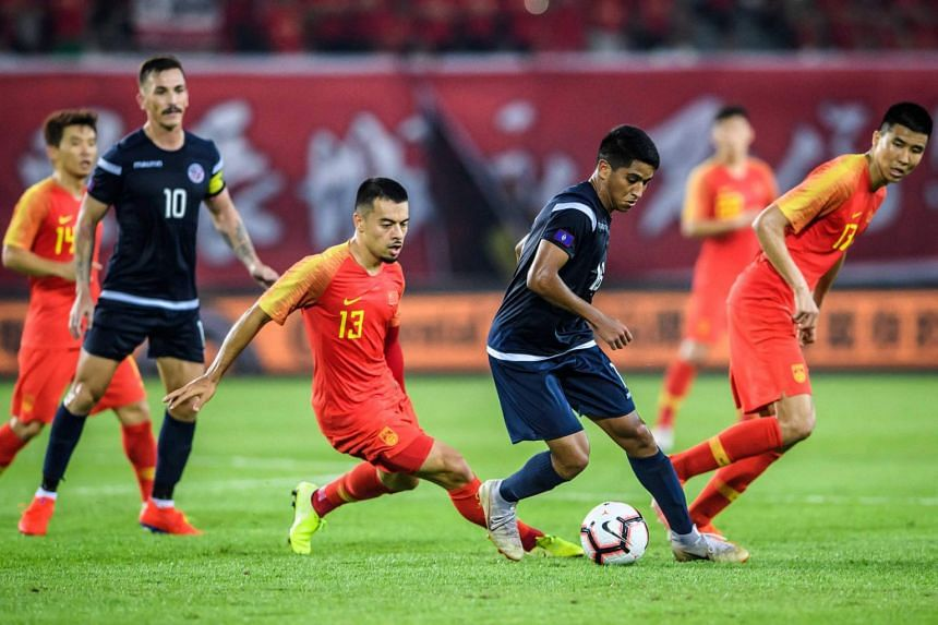 Li Ke (left) and Devan Jakob Mendiola during the 2022 World Cup football qualifier between China and Guam in Guangzhou, on Oct 10, 2019.