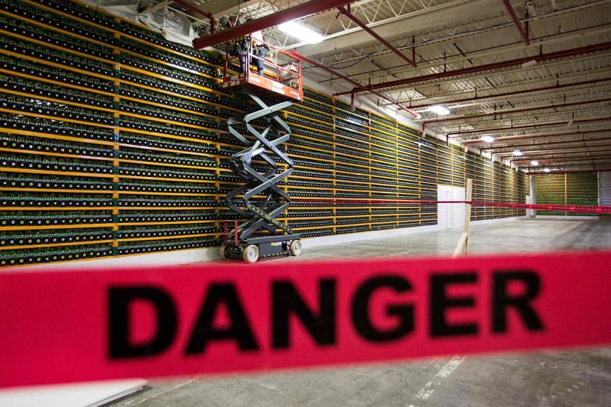 Two workers using an extendable lift along a wall of Bitcoin mining at Bitfarms in Saint Hyacinthe, Canada, on March 19, 2018.