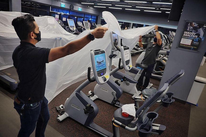 Staff covering up treadmills in the True Fitness gym at HarbourFront Centre on May 7, the last day before tighter measures kicked in. Eligible gyms and fitness studios can tap 50 per cent wage support under the Jobs Support Scheme from May 16 to June