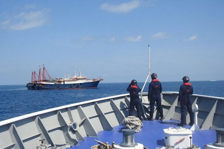 In a photo taken on April 27, 2021, Philippine Coast Guard personnel survey several ships believed to be Chinese militia vessels in Sabina Shoal in the South China Sea.