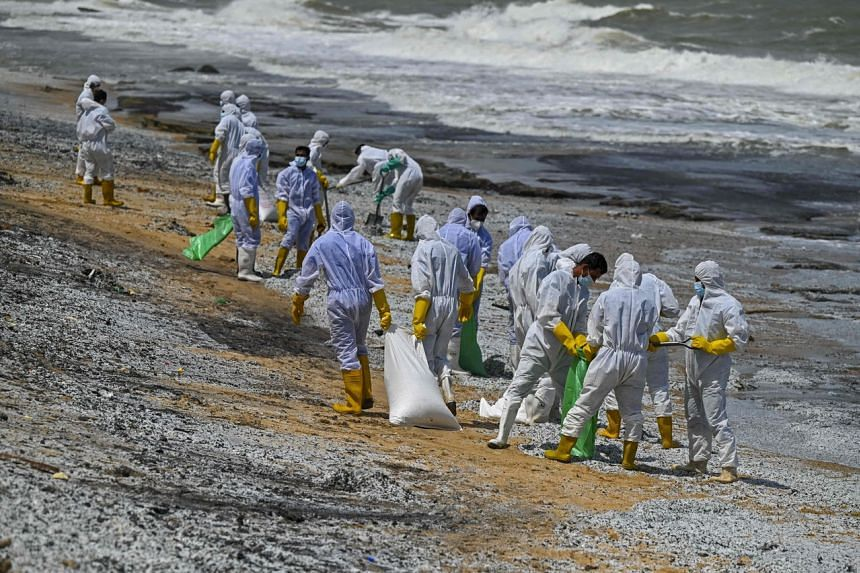 Sri Lankan navy soldiers work to remove debris washed ashore on a beach in Colombo, on May 29, 2021.