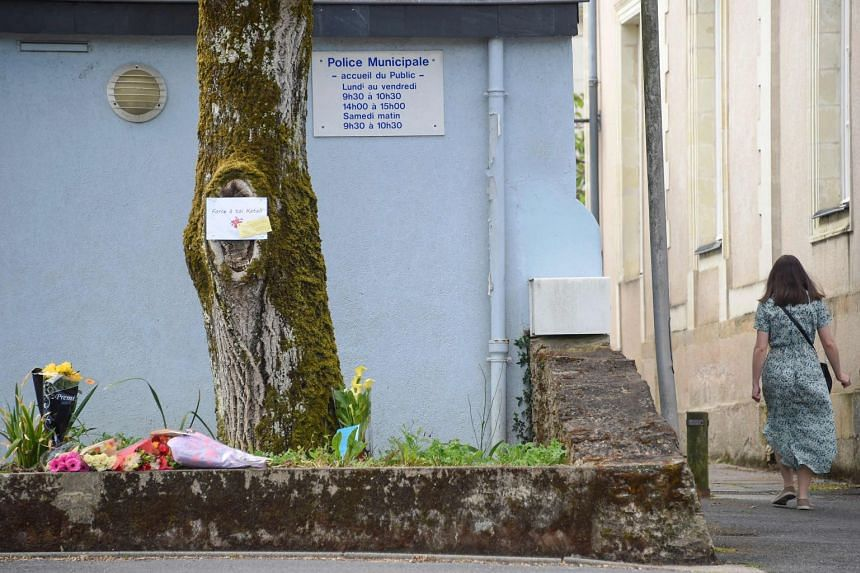 A woman walks past bunches of flowers laid down where the female police officer was stabbed.