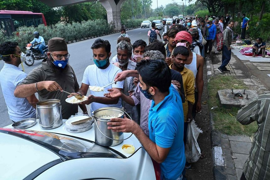 Homeless people queue up as volunteers distribute food along the roadside in New Delhi on May 20, 2021.