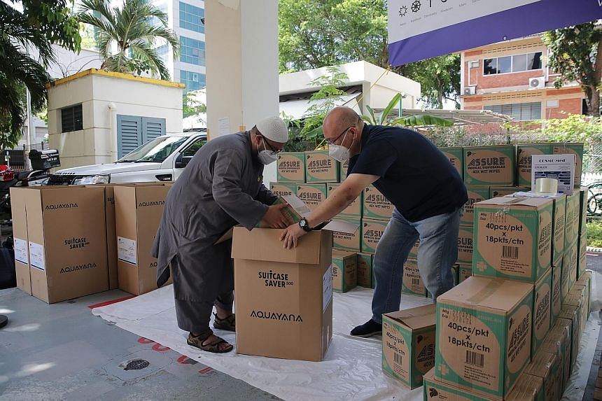 Volunteers Ustaz Muslim Ahmad (far left), 30, a Community Engagement and Youth Development officer at Al-Muttaqin Mosque, and Dennis Khoo, 54, secretary-general of the International Multi Cultural Organisation, getting relief items ready for dispatch