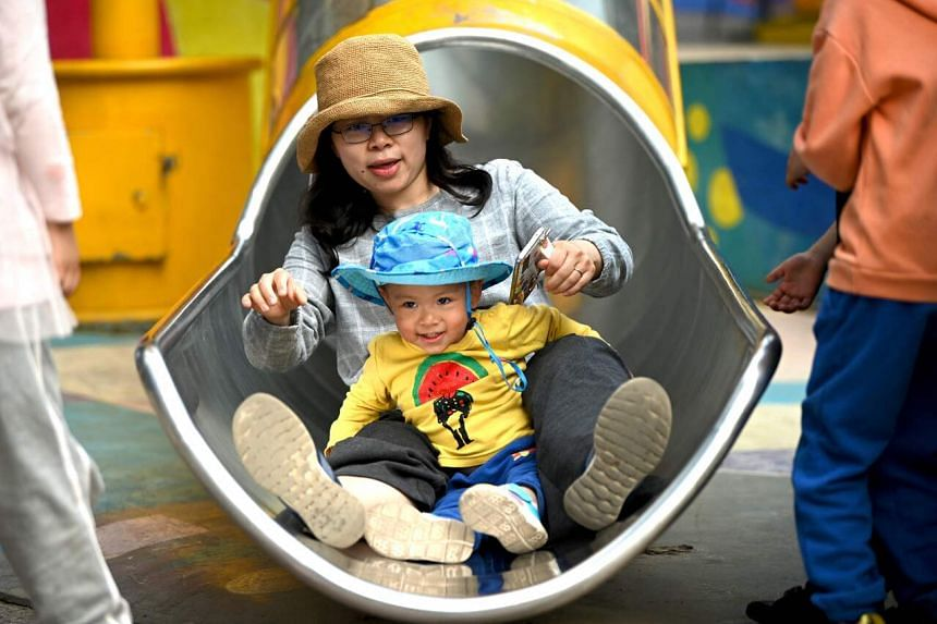 A mother and her baby play on a slide in Beijing on May 11, 2021.
