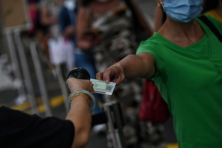 A foreign domestic worker getting her identification card scanned for entry to Lucky Plaza in April.