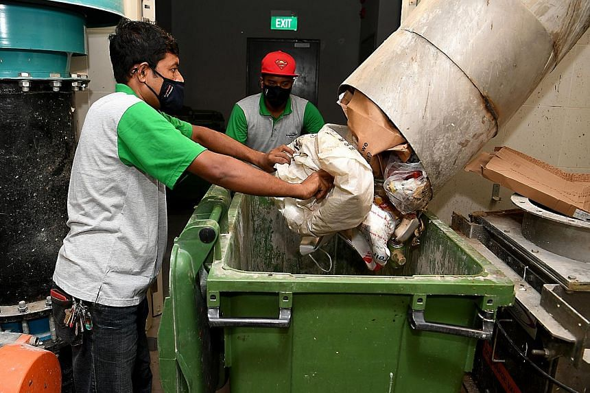 Workers collecting waste manually at Alkaff CourtView last month. The volume of improper waste disposal at three of the project's blocks has dropped, enabling the resumption of the automatic waste system, HDB said. ST PHOTO: KHALID BABA