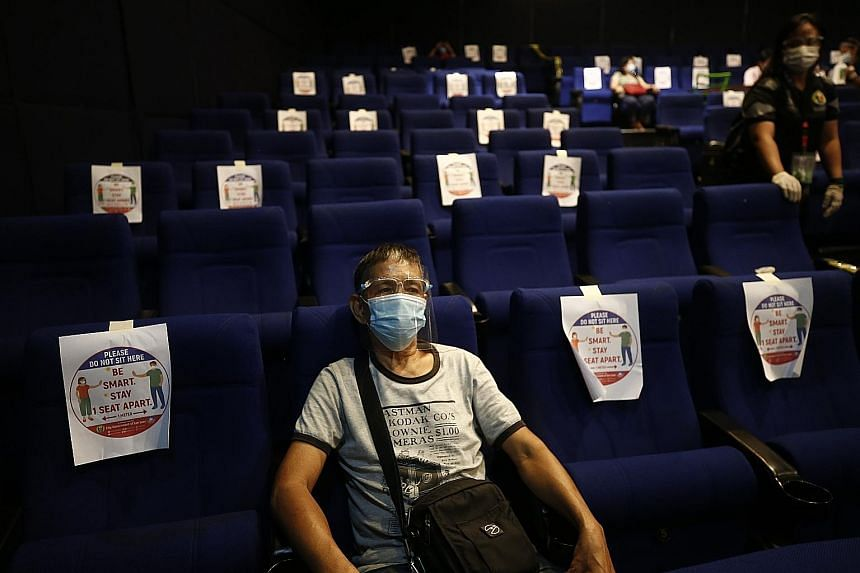 A Filipino resting inside a cinema after being inoculated with the Sinovac Covid-19 vaccine in San Juan City, Metro Manila, yesterday. Malls that have been providing space for the vaccine roll-out have been offering banana fritters and free parking.