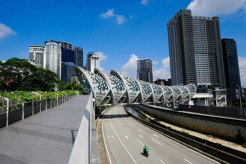 A Grab delivery rider approaching the Saloma Link bridge on a near-empty highway in the Malaysian capital, Kuala Lumpur, yesterday. Under the full movement control order that began yesterday and will last until June 14, most economic and social activ