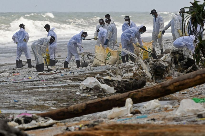 Members of the Sri Lankan Navy (top) removing debris washed ashore from the X-Press Pearl (above) on a beach in Colombo on Monday. The ship, which had nitric acid and other chemicals on board, was on its way to Singapore from India when the fire brok