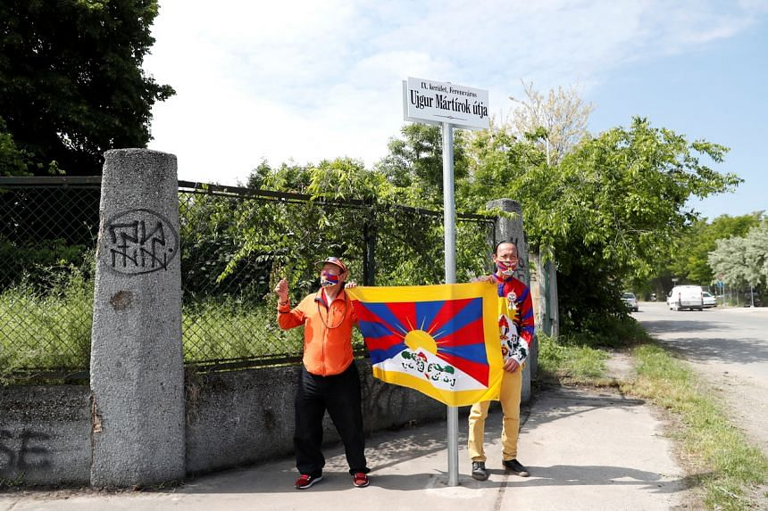 """Activists next to a sign in a street renamed """"Martyrs of Uighur"""" in Budapest on June 2, 2021."""