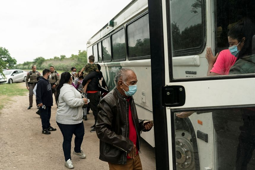 Asylum-seeking migrants' families from Venezuela board an US Border Patrol's bus to be transported into the United States from Mexico in Del Rio, Texas, on May 27, 2021.
