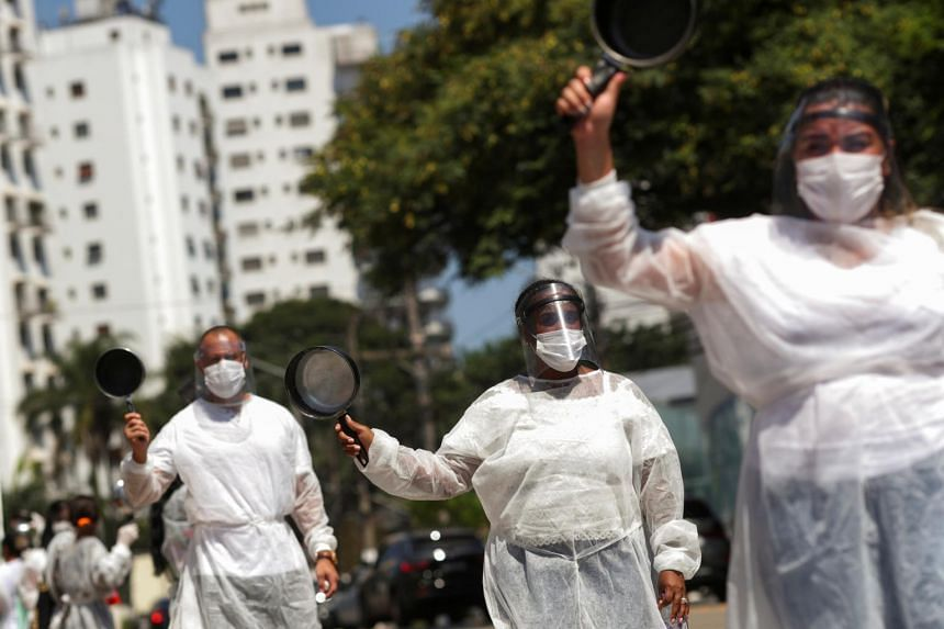 Residents of Paraisopolis holding pots during a protest amid the Covid-19 pandemic in Sao Paulo on March 26, 2021.