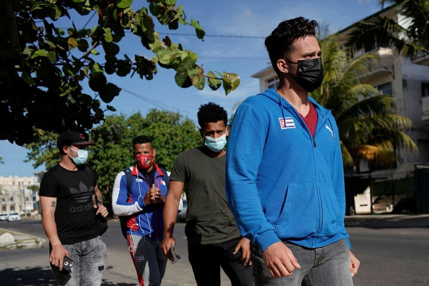 In this photo taken on May 19, 2021, Cuba's national baseball team Cesar Prieto (far right) and teammates walk towards the US for visa procedures in Havana.