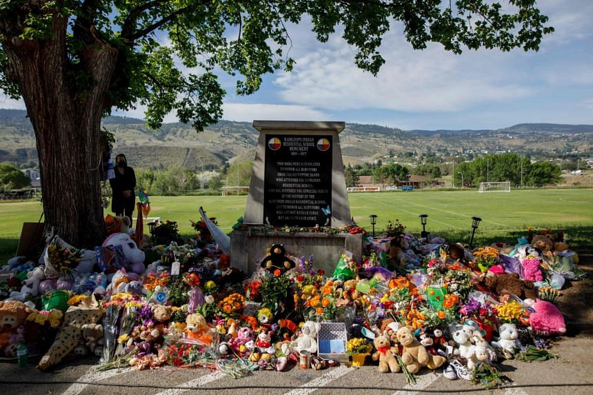 A makeshift memorial honouring the 215 children surrounds a monument outside the former Kamloops Indian Residential School on June 2, 2021.