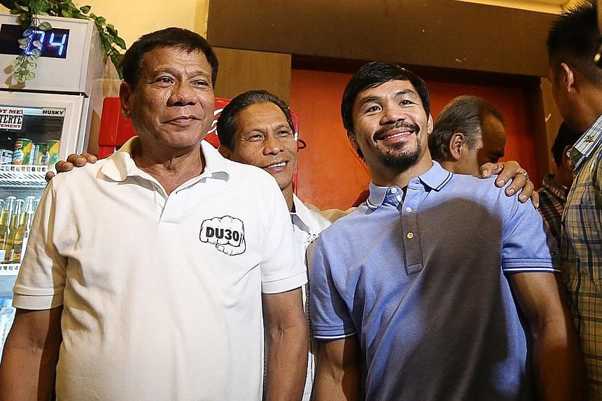 A 2017 photo of Philippine President Rodrigo Duterte (left) with boxing icon and newly elected Senator Manny Pacquiao in Davao. PHOTO: AGENCE FRANCE-PRESSE