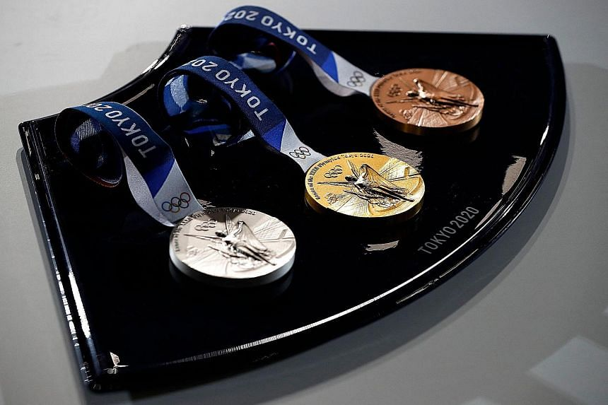 The medals and tray to be used for the medal ceremonies at Tokyo 2020 are seen at an event to mark 50 days to the opening ceremony. The tray is produced using recyclable thermoplastic polymer.