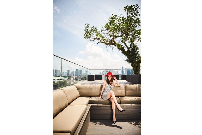 Beauty entrepreneur Kim Lim – wearing her own Dior dress, Saint Laurent by Anthony Vaccarello hat and pumps and gold jewellery – at the rooftop of her home (above).