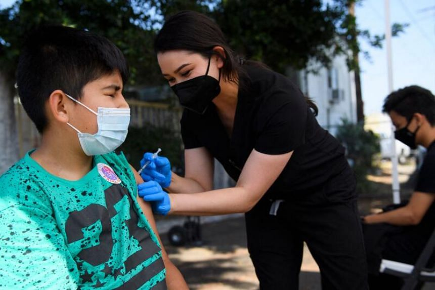 Jair Flores, 12, receives a first dose of the Pfizer Covid-19 vaccine at a mobile vaccination clinic at the Weingart East Los Angeles YMCA in the United States on May 14, 2021.
