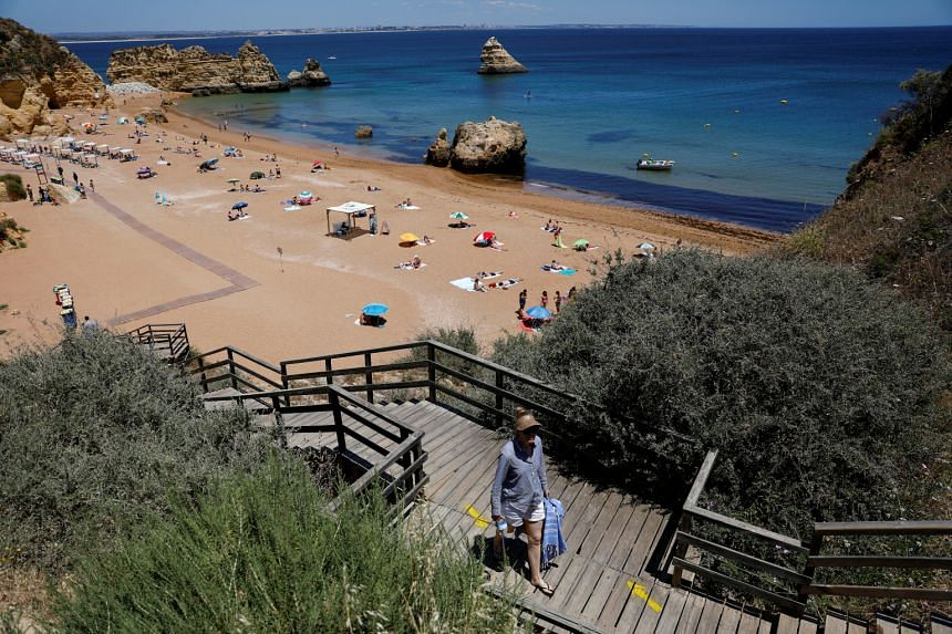 A woman leaves the Dona Ana beach in Lagos, Portugal, on June 3, 2021.