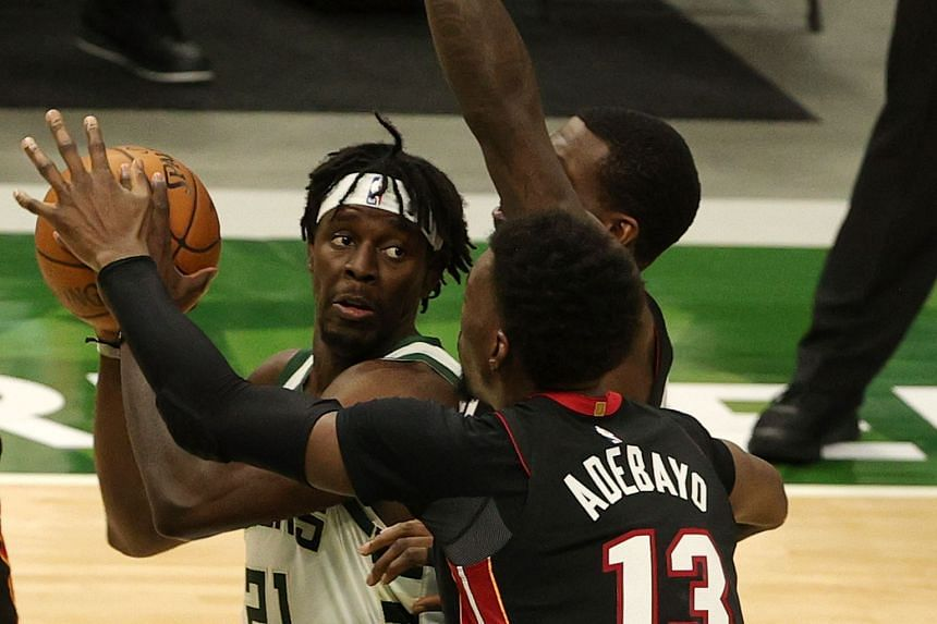Jrue Holiday of the Milwaukee Bucks (far left) in action against Miami Heat players Bam Adebayo (#13) and Kendrick Nunn on May 15, 2021 in Milwaukee, Wisconsin.
