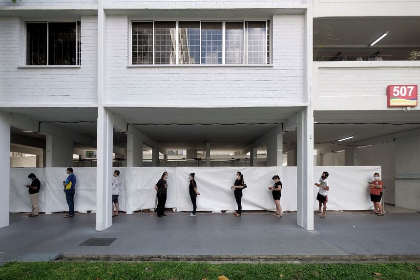 Residents and workers from nearby blocks queue for mandatory Covid-19 testing at the void deck of Block 507 Hougang Avenue 8, on June 4, 2021.