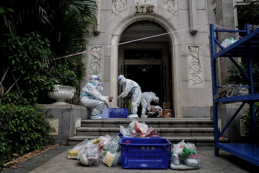 Property management workers deliver goods to residents at a compound under lockdown in Guangzhou on June 2, 2021.