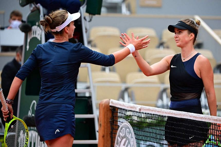 Barbora Krejcikova (left) and Elina Svitolina shake hands at the end of their women's singles third round tennis match at the French Open in Paris, on June 5, 2021.