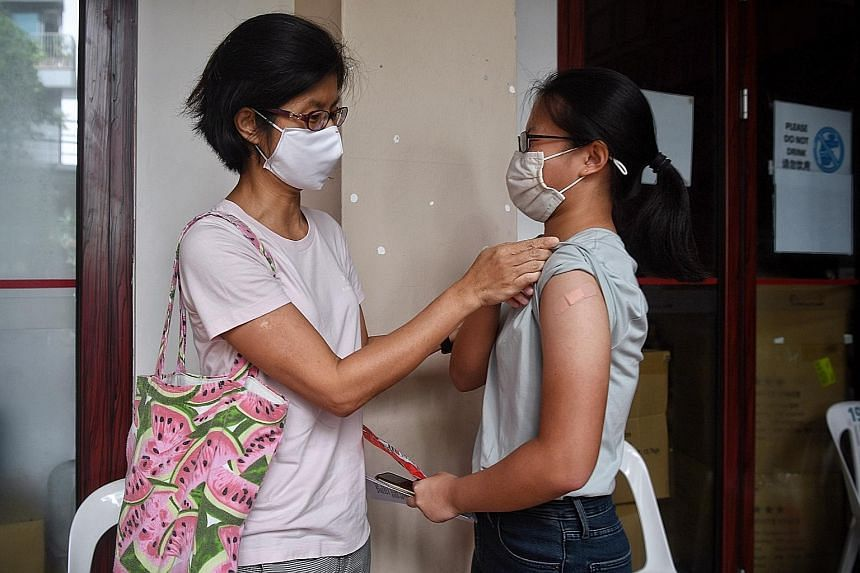 Consultant Stacey Ng (left) was among many parents who accompanied their children to their vaccination appointments at Tanjong Pagar Community Club (above) and other centres. Her daughter Heidi did not experience any side effects. Sisters Chia Sin Ji