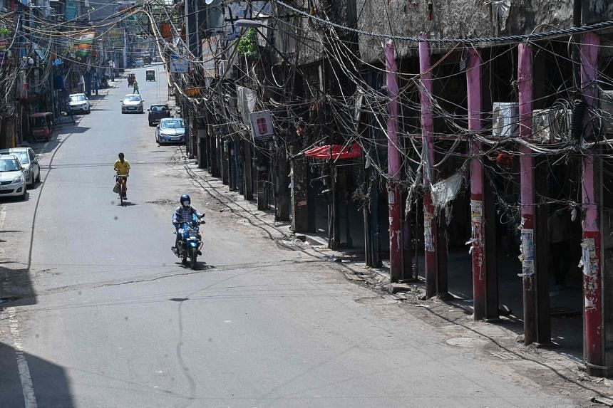 Motorists making their way through a partially deserted closed market in New Delhi on Saturday.