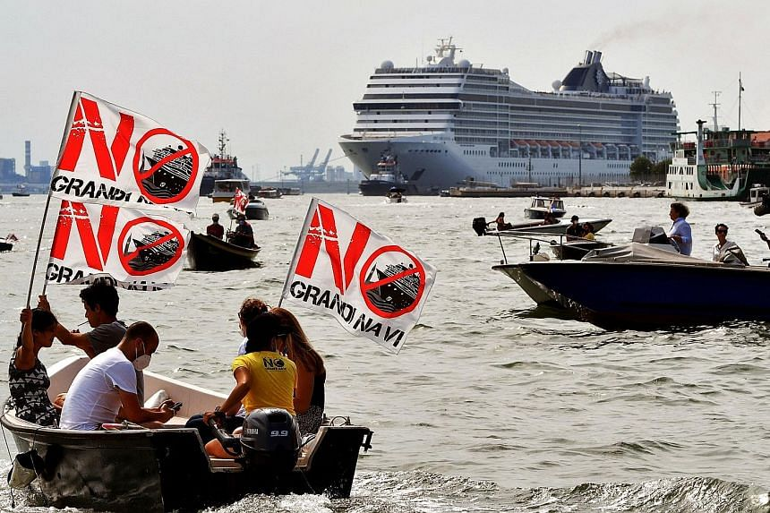 Demonstrators in motorboats protesting against the presence of cruise ships in the lagoon, as the MSC Orchestra cruise ship (background) leaves Venice. Concerned for the environment and the city's cultural heritage, opponents of the ships say they ca