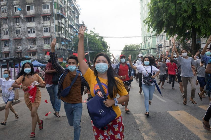 Anti-coup protesters flash the three-finger salute during a flash mob protest in Yangon on June 3, 2021.
