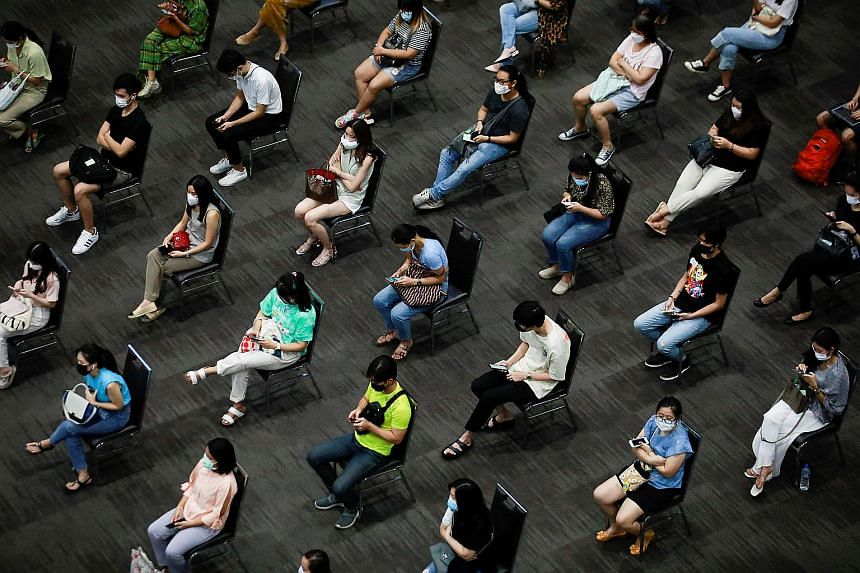People wait to receive a shot of the AstraZeneca vaccine at a gymnasium inside the Siam Paragon shopping center in Bangkok on June 7, 2021.