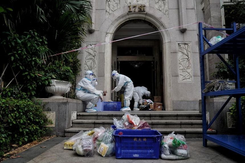 Workers deliver goods to residents at a compound under lockdown in Guangzhou on June 2, 2021.