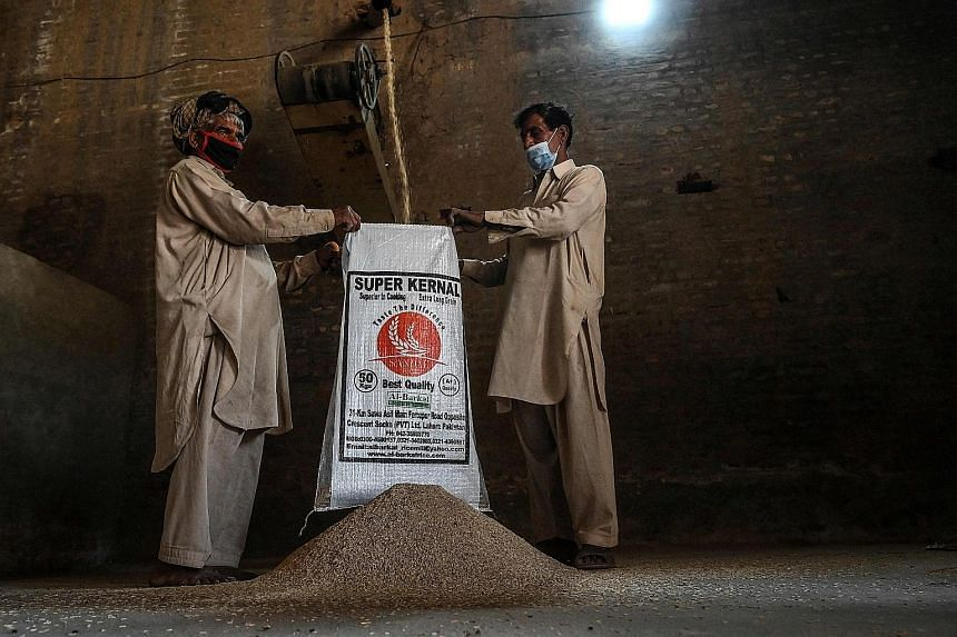 Workers at the Al-Barkat Rice Mills on the outskirts of Lahore, Pakistan. The country is opposing India's move to gain an exclusive trademark - protected geographical indication - for its basmati rice from the European Commission.