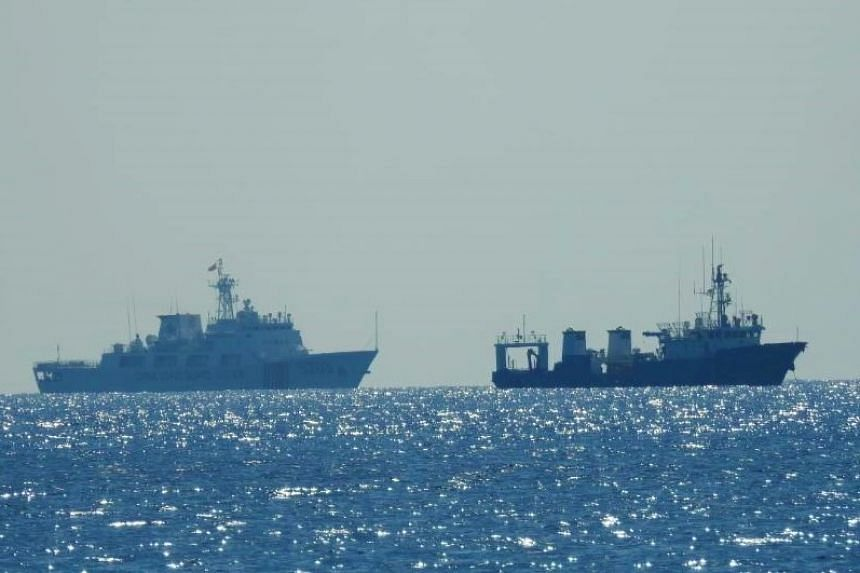 A Chinese Coast Guard patrol ship (left) is seen near an unidentified vessel at Whitsun Reef, in the South China Sea, in a photo released by the Philippine Coast Guard on April 15, 2021.