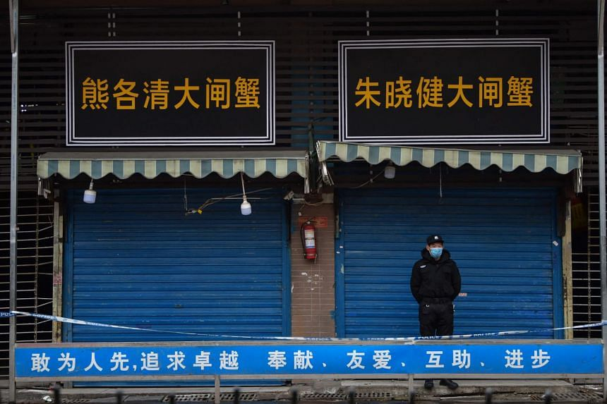 A security guard stands outside the Huanan Seafood Wholesale Market in Wuhan, on Jan 24, 2020.