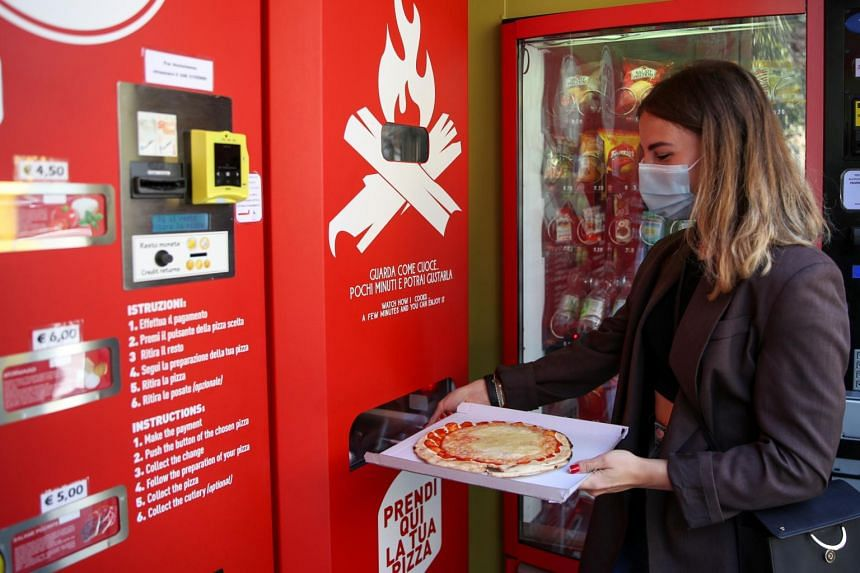 Ms Fabrizia Pugliese collects her order at the first automatic pizza vending machine in Rome on May 6, 2021.